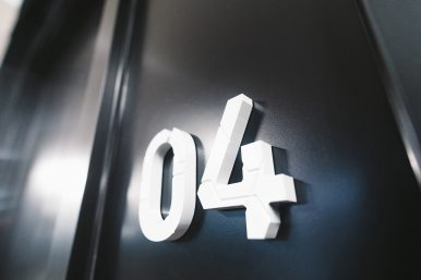 0 and 4 white 3D numbers affixed to a black wall