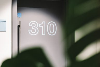 Cut vinyl door numbers on a black office door