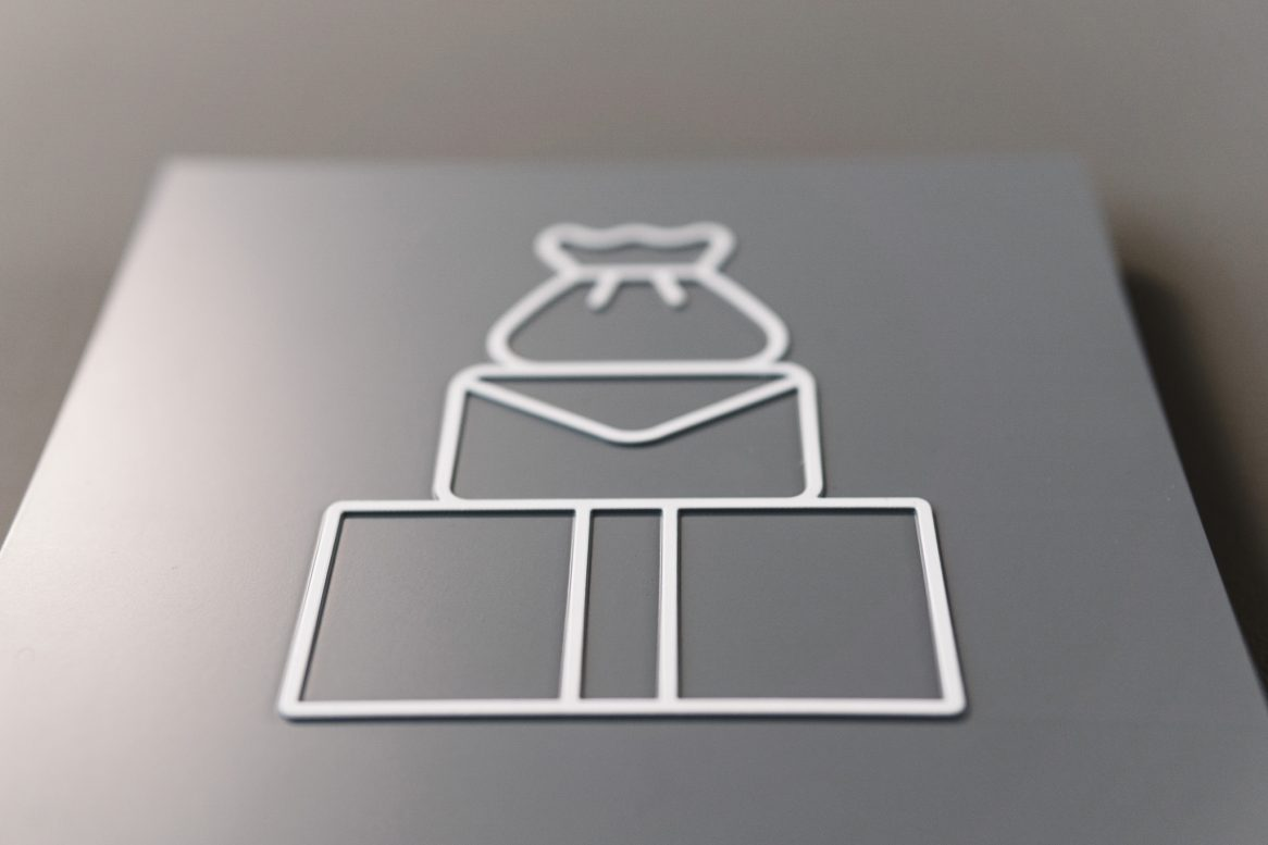 Picture of a top section of a grey braille wayfinding sign featuring a braille design