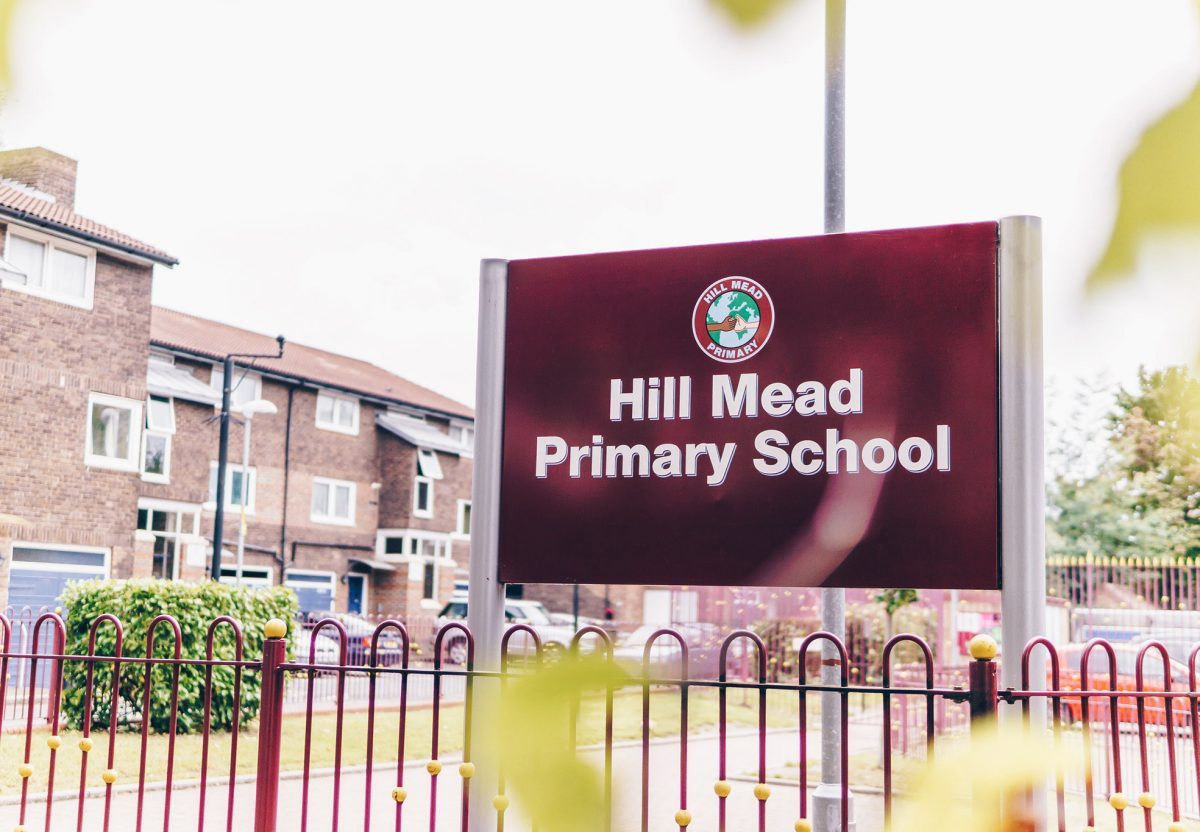 Dark red large metal school sign with zinc post installed at the entrance of the school