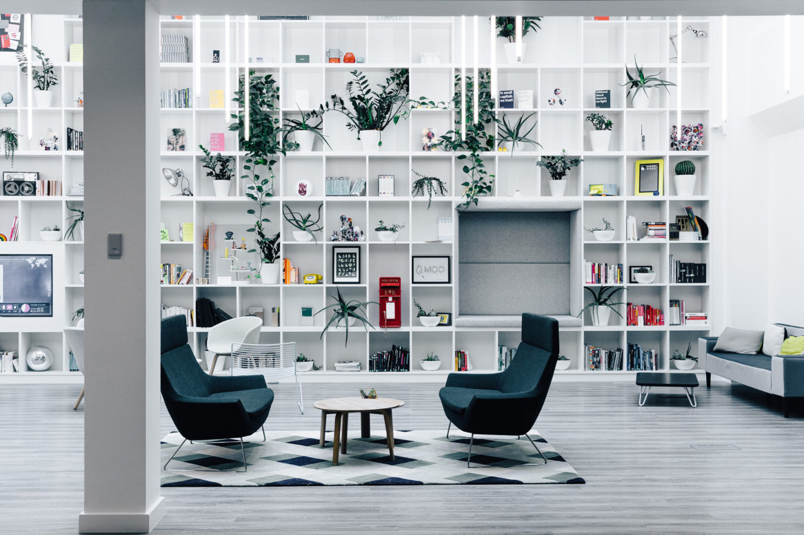 The black and white themed is used in a seating area with an airy backdrop of wall to ceiling white shelving.