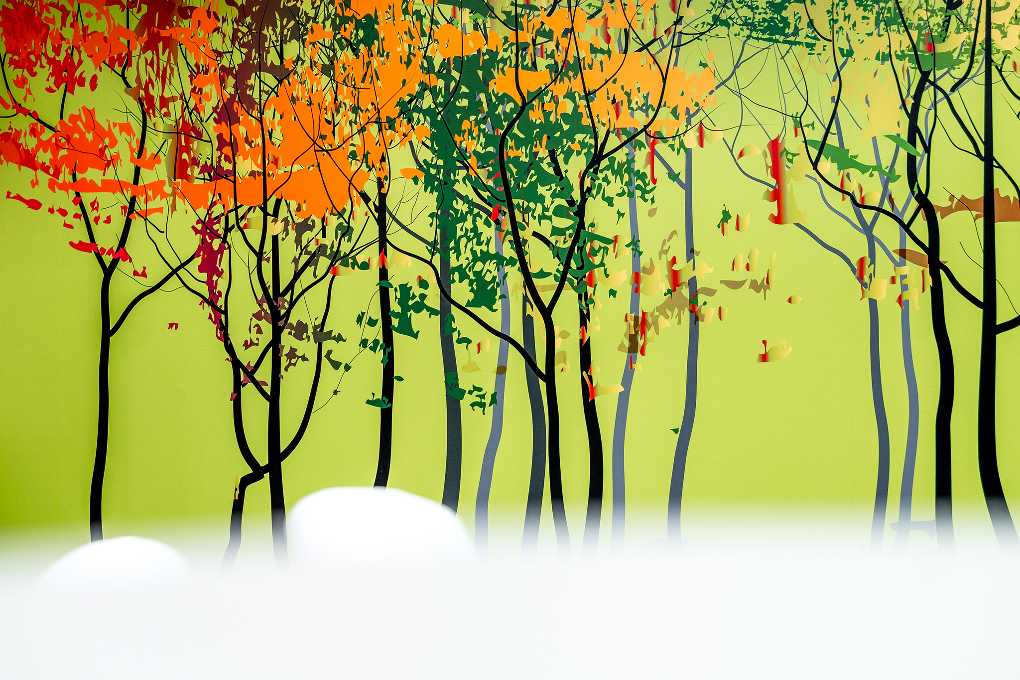 Vinyl wallpaper of autumn trees on a lime green background.