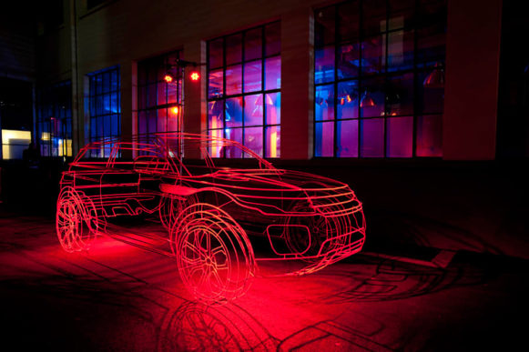 One of Ben's car wireframe sculptures displayed indoors in warm red lights.