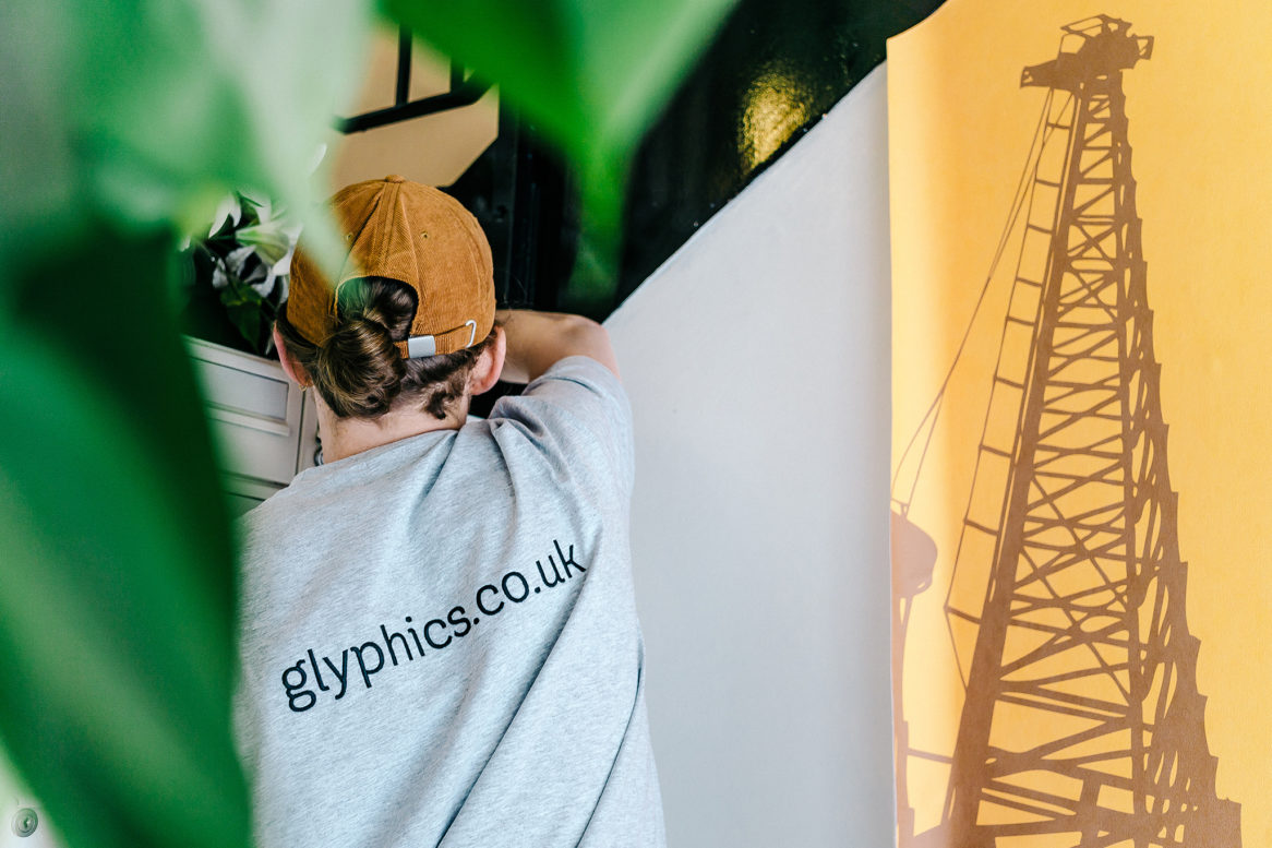 Glyphics installer applying wallpaper on an angled wall.