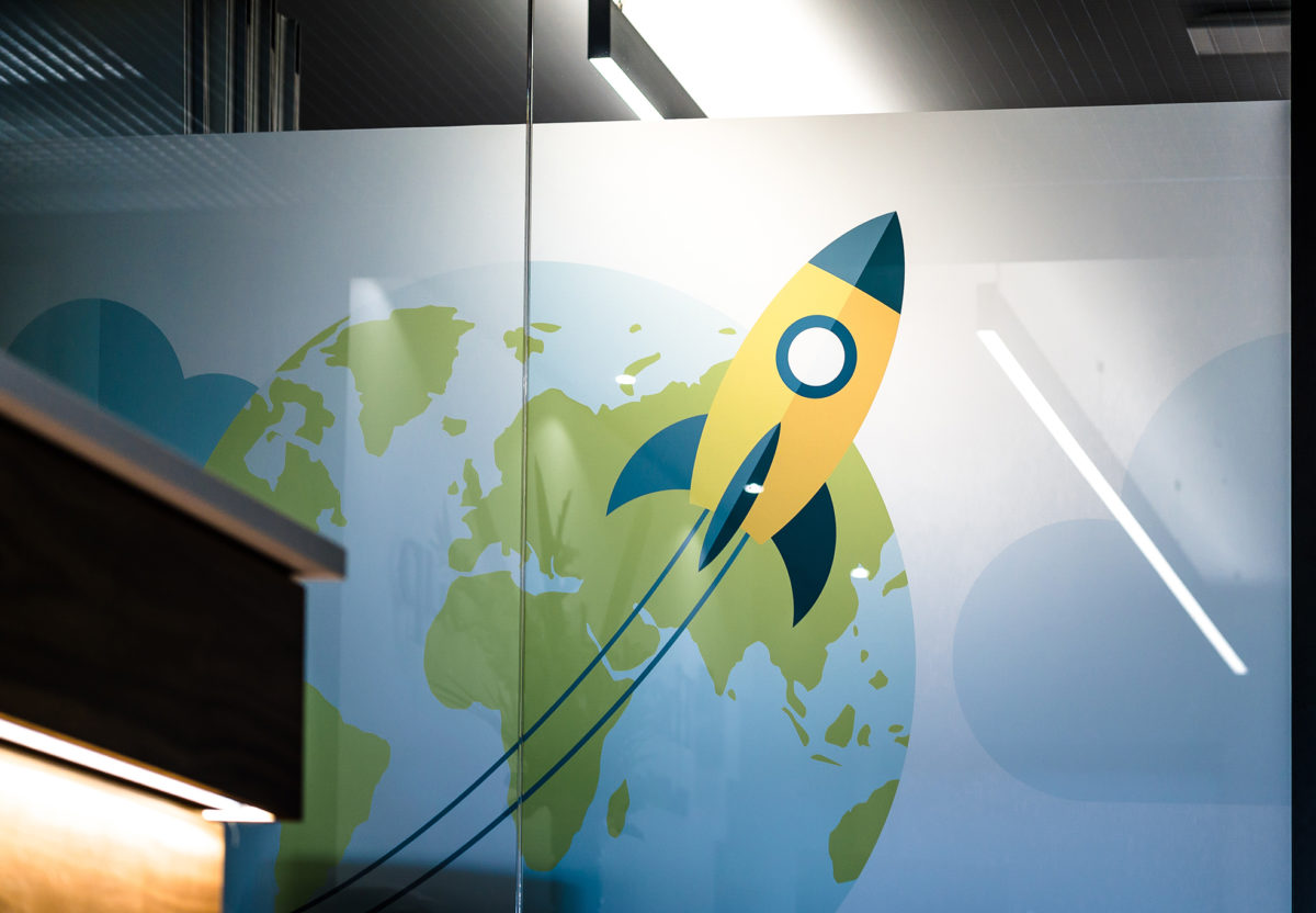 A fun yellow and blue rocket part of the office glass manifestation of the Hackett Group.