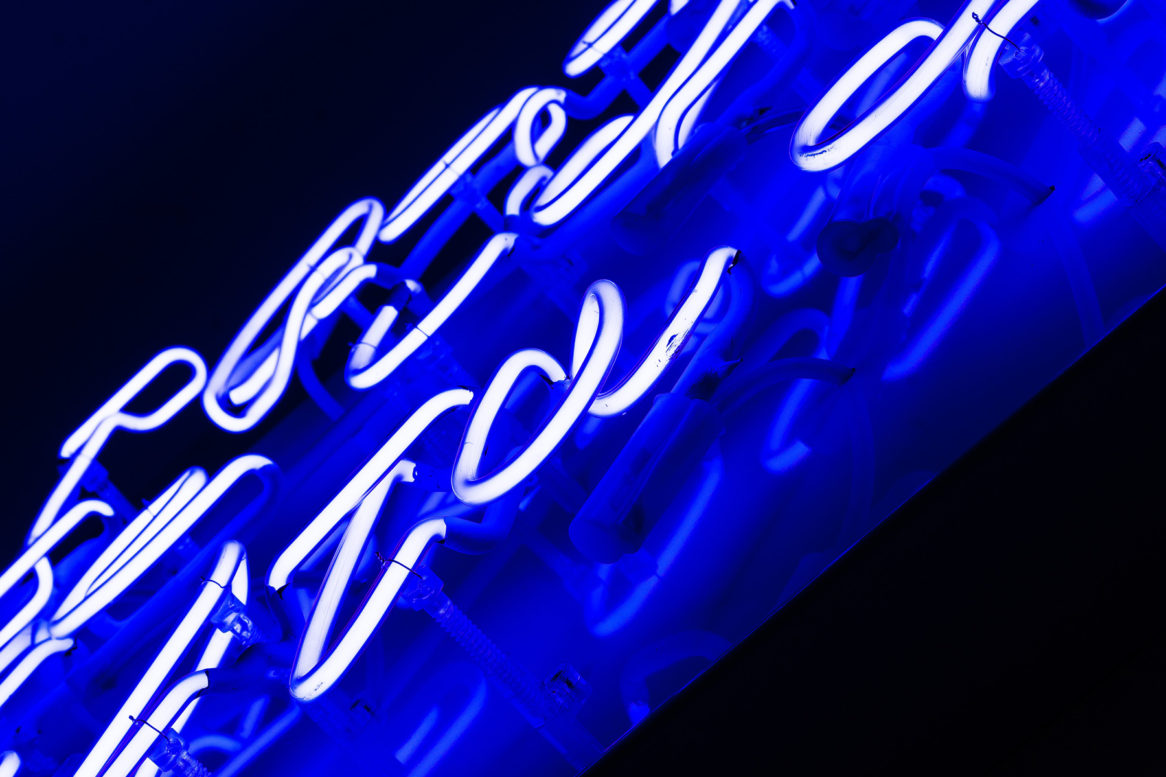 Close up of blue neon lettering.