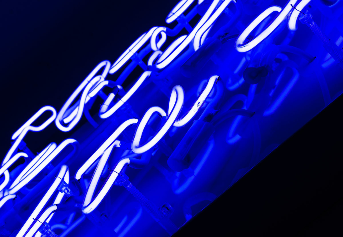Close up of the Blue Raincoat neon sign.